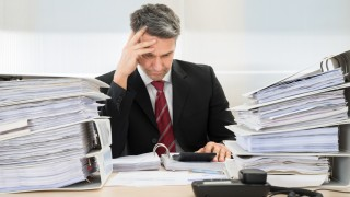 Businessmann arbeitet am Schreibtisch mit Aktenrodnern