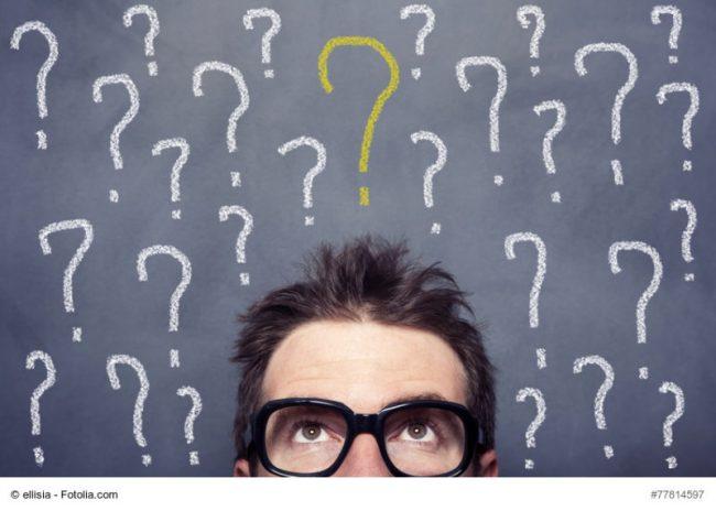 Eine Tafel mit Fragezeichen, vor der ein Mann mit Brille steht und fragend nach oben blickt