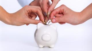 4 Personen stecken Münzen in ein Sparschwein