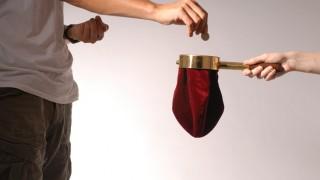 Mann wirft Münze in Klingelbeutel