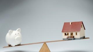 Sparschwein und Hausmodell auf einer Waage