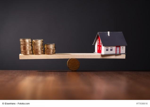 Geld und Hausmodell auf einer Waage