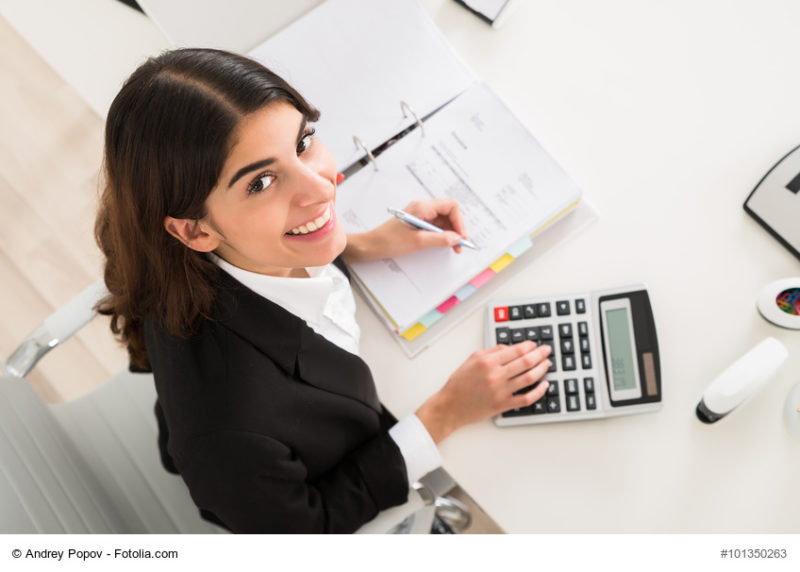 Happy Businesswoman Doing Financial Calculation At Desk