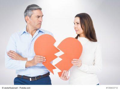 Paar hält ein durchgeschnittenes Herz aus Pappe