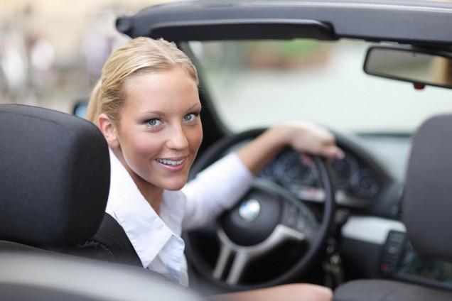 Frau sitzt in einem Cabrio am Steuer