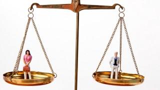 Mann und Frau auf Waage.Symbol für Gleichheit, Recht, Finanzen