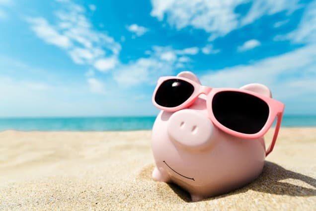 Ein Sparschwein mit Sonnenbrille am Strand