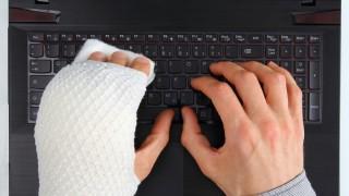 Eingebundene Hand über Tastatur