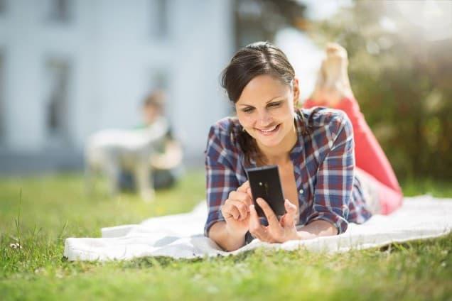 Frau liegt mit Smartphone auf Wiese