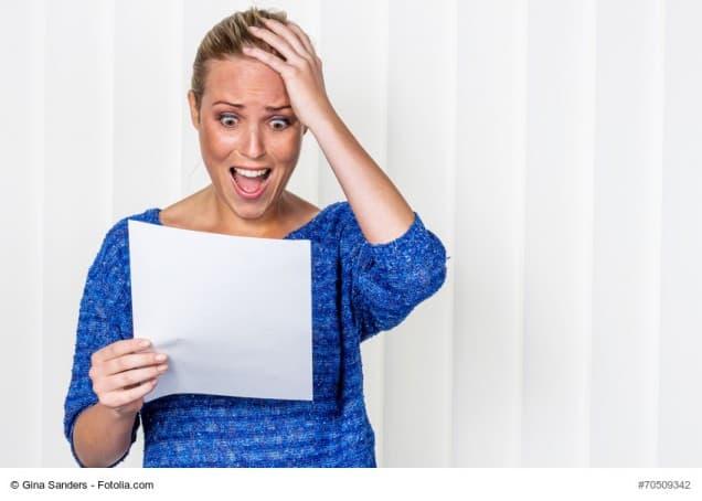 Frau schaut entsetzt auf Brief