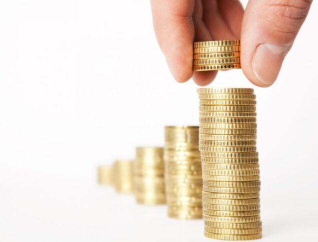 Hand stapelt Münzen auf Stapel