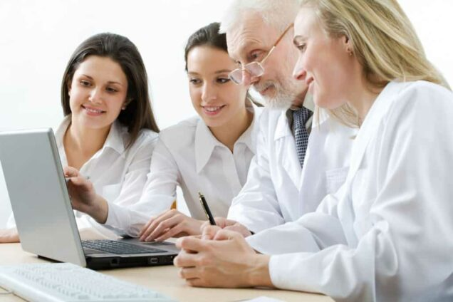 Ärzteteam blickt in Laptop