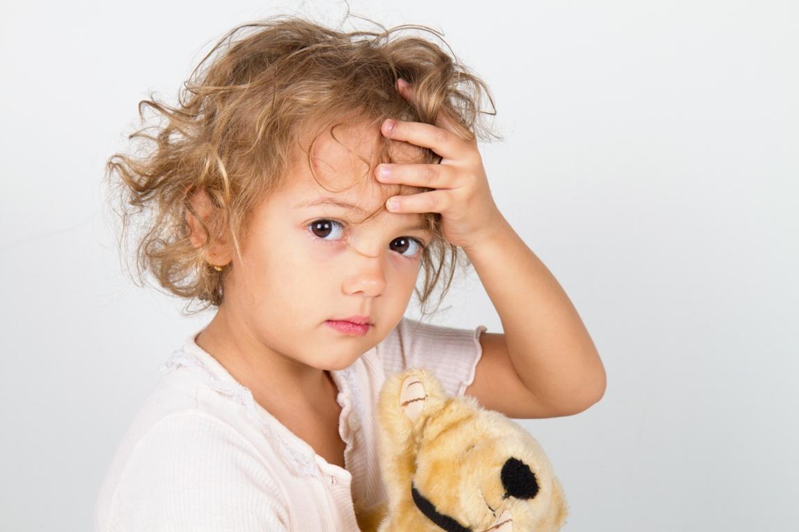 Kind mit teddy hält sich den Kopf