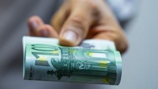 Hand hält Geldscheine in die Kamera