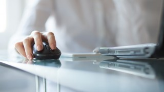 Businesswoman clicking on cordless mouse