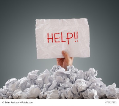 """Eine Hand hält ein Schild mit der Aufschrift """"Help"""" aus einem Haufen zerknülltem Papier"""
