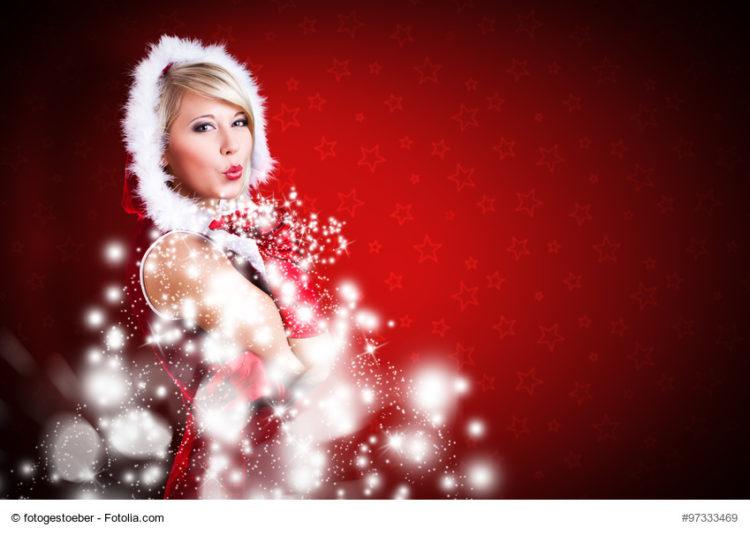 attraktive Miss Santa pustet Schneeflocken
