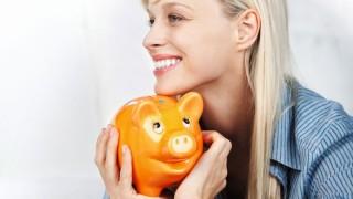 attraktive frau hält sparschwein in der hand