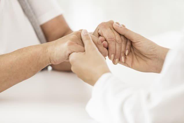 Arzt hält Hände der Patientin