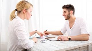 Frau und Mann sitzen über Unterlagen und stellen Berechnungen an