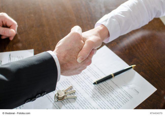Händeschütteln über einem Vertrag zur Praxisübernahme.