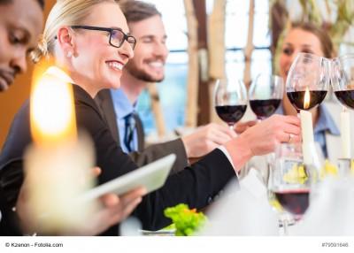 Leute, die an einem Tisch sitzen und mit Weingläsern anstoßen