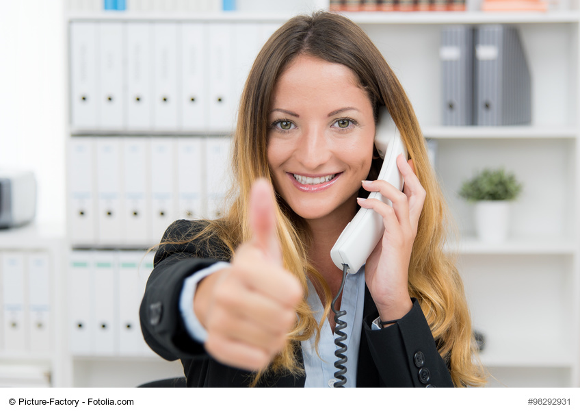 geschäftsfrau macht einen deal am telefon und zeigt daumen