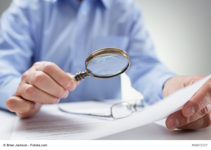 Businessman with magnifying glass reading documents
