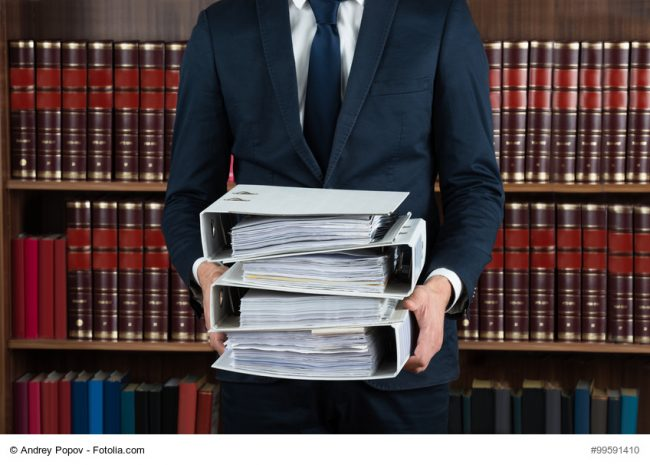 Lawyer Carrying Stack Of Ring Binders