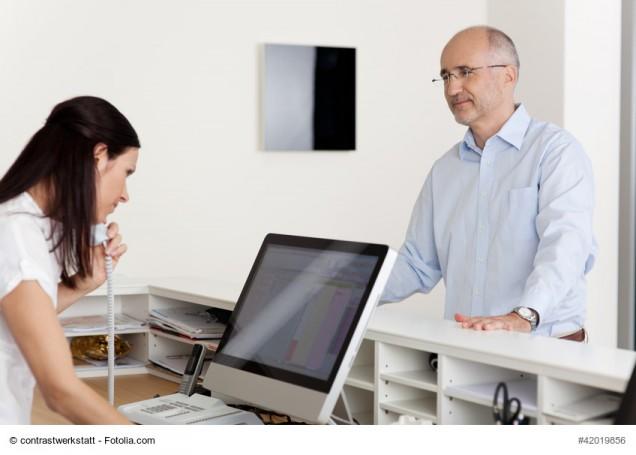 Arzthelferin schaut in den Computer