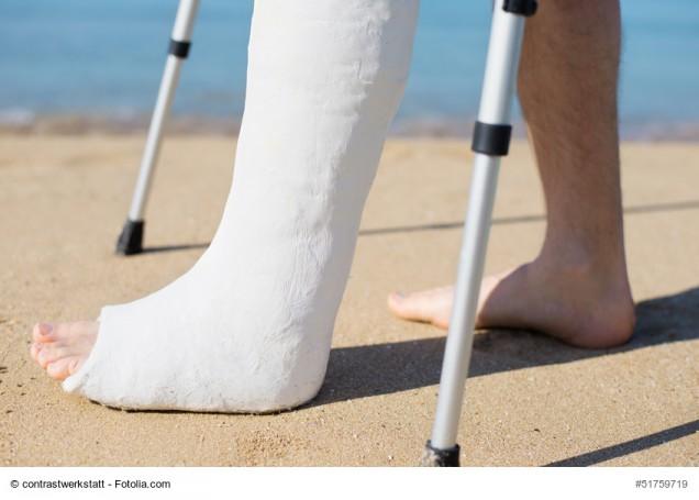 Mann geht mit Gipsbein am Strand