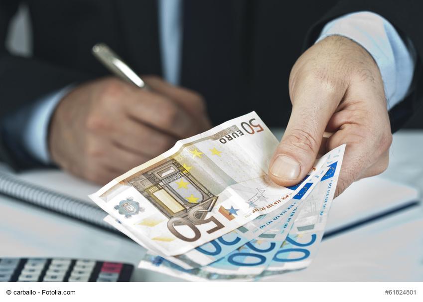 Mann zählt Geld und macht sich Notizen