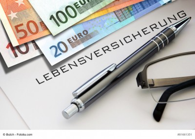 Kugelschreiber und Geldscheine auf einem Formular mit der Aufschrift Lebensversicherung