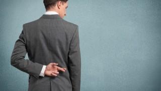 Mann überkreuzt Finger hinter Rücken