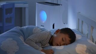 Kind liegt im Bett und schläft, neben dem Bett steht ein Luftreiniger von Philips
