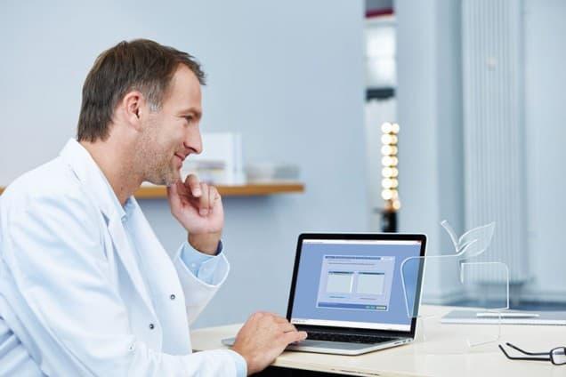 Arzt schaut auf Laptop mit Abrechnungssoftware