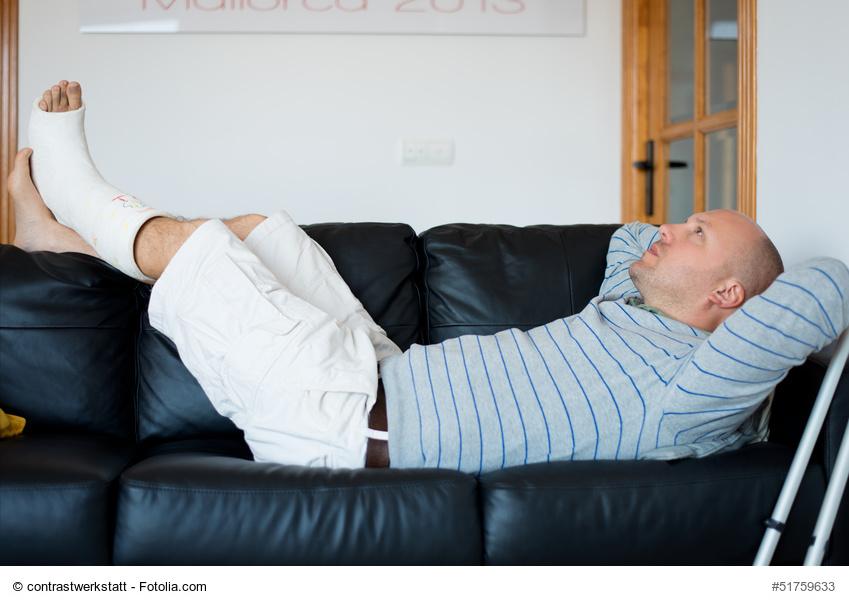 mann mit gips liegt auf dem sofa