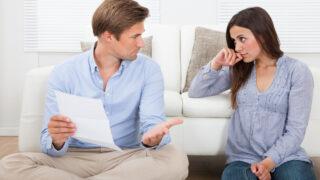 Ehepaar diskutiert über Schriftstück, das der Mann in der Hand hat