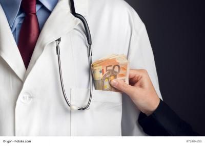 Hand steckt dickes Geldbünden in Brusttasche vom Mann im Arztkittel