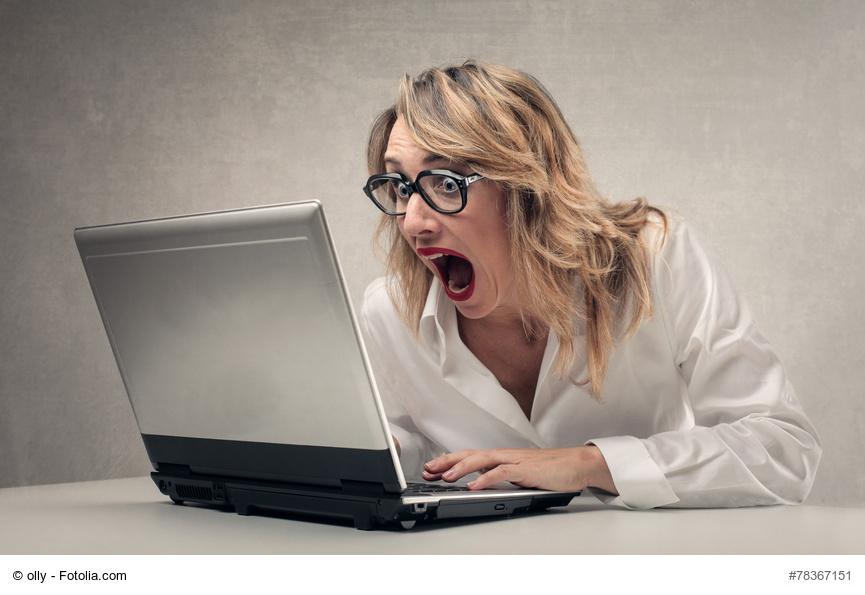 Frau schaut entsetzt auf PC-Monitor