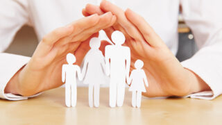 Zwei Hände, die sich schützend über eine Familie stülpen