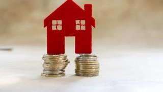 Hausmodell aus Filz steht auf Münzen