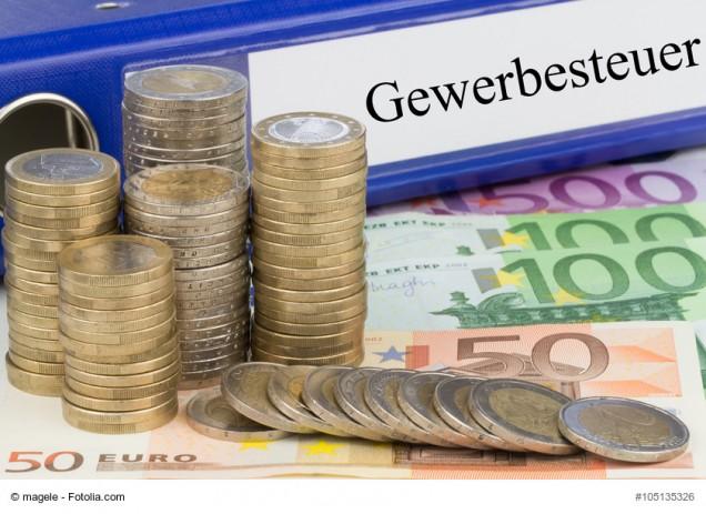 Aktenordner mit Schriftzug Gewerbesteuer und Münzen und Geldscheine