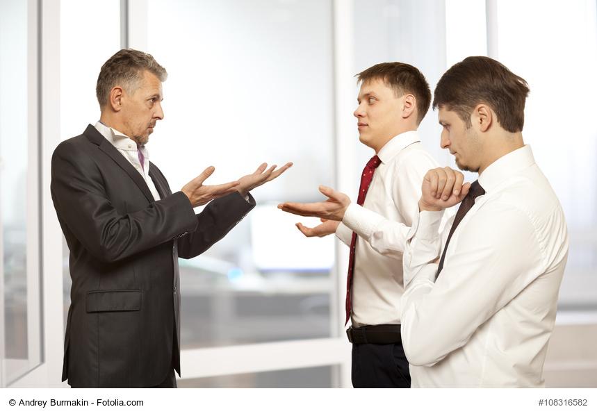 Mann im Anzug spricht mit 2 jungen Männern, die mit den Schultern zucken