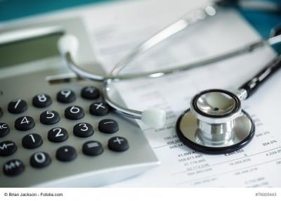 Stethoskop neben Taschenrechner und Bilanz