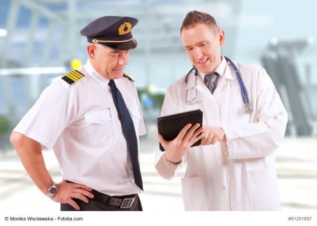 Arzt zeigt Pilotem etwas auf dem Tablet