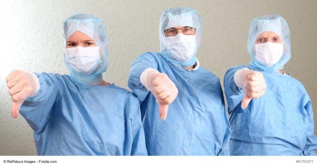 Drei Ärzte im OP mit Daumen nach unten