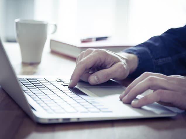 Männerhände tippen auf Laptop-Tastatur