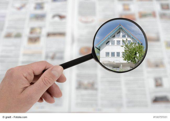Immobilenanzeigen in Zeitung mit Lupe betrachtet