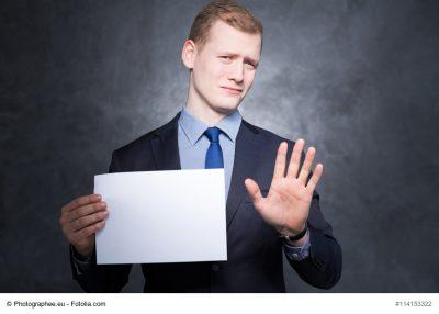 Mann hebt abwehrend die Hand und hält ein Dokument fest